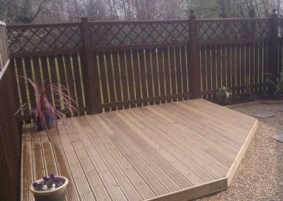 A small decked area with freshly painted fencing to surround.