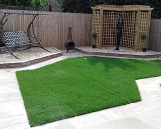 A complete garden revamp with sandstone patio areas and paths, new lawn and pergola area with water feature.