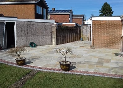 A large Indian sandstone patio area with a drainage channel incorporated.