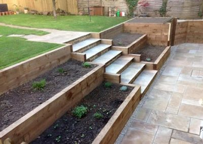 A tiered garden using timber sleepers to form raised beds, and Indian sandstone for the steps and paved areas