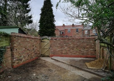 A large wall re-built using reclaimed bricks, with archway and new gate