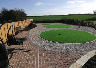 A large garden revamp with a block paved patio area, granite setts used to retain new plant beds, shingle and circular artificial lawn areas