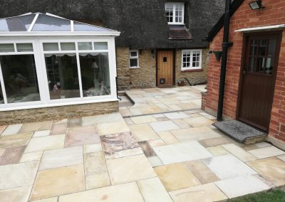 An Indian sandstone patio area with french drain for drainage.