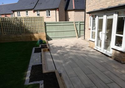 A porcelain patio area with raised beds to surround, trellis and new lawn.
