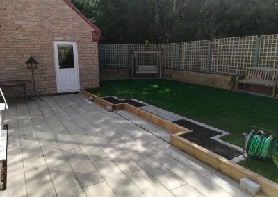 A porcelain patio area with raised beds to surround, trellis and new lawn