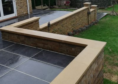 A terraced porcelain patio area with brickwork to retain, and capped with a light stone