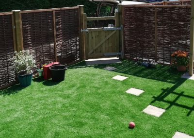 An artificial lawn with stepping stones within.