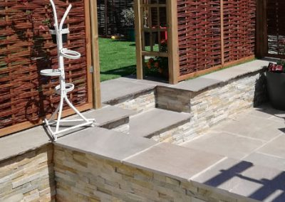 A suntrap area built and retained in stone, with Indian sandstone the slab of choice selected to compliment.