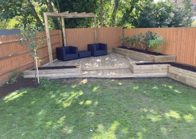 A decked area with integrated raised beds and pergola feature.